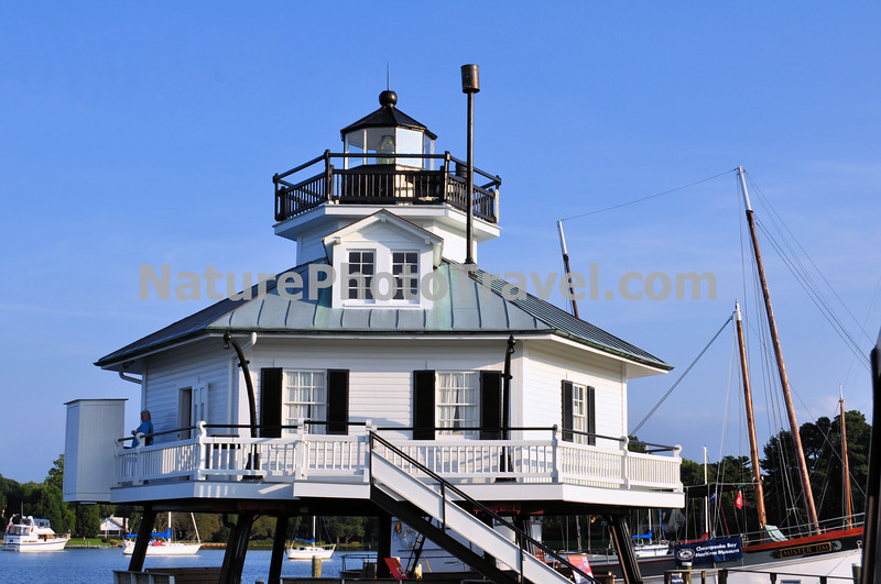 Hooper Straits Lighthouse, St. Michael's, MD<br /> (and the Maritime Museum)<br /> <br /> The entrance to Tangier Sound was marked with a lightship from 1827 or 1828 to 1845. The first lighthouse was constructed in 1867 and destroyed by ice during the winter of 1877. <br /> <br /> The second screwpile lighthouse was constructed in 1880.  The structure was designed and built in Baltimore, then dismantled and re-erected at the site in October of that year. It had a fifth-order fresnel lens. Keepers were not allowed to have family living at this lighthouse. Water for drinking, bathing and cooking was collected from the roof's rain gutters, groceries were rationed and arrived once a week from the mainland, and the bathroom facilities were located outside on the deck. <br /> <br /> The lighthouse was slated for destruction in 1966 when it was acquired by the Chesapeake Bay Maritime Museum in St. Michaels, MD. The move required the lighthouse being was cut from its original pilings and cut in half befor being transported up the Bay to its new site in November of that year.   It is open to the public. <br /> <br /> St. Michael's was once a very important center for shipbuilding and seafood harvesting.   But today it is mainly known as a vacation stop with charming Inns, fine restaurants and unique antique shops. The Maritime Museum is still a vital part of the town. The musum operates a shipyard and ship building facility for restoration, and the relics of life and work on the Chesapeake are meticulously maintained.