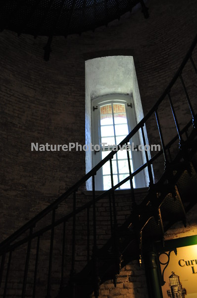 "Currituck Beach Lighthouse (Interior)<br /> On December 1, 1875 the beacon of the Currituck Beach Lighthouse filled the remaining ""dark space"" on the North Carolina coast between the Cape Henry light to the north and Bodie Island to the south. To distinguish the Currituck Beach Lighthouse from other regional lighthouses, its exterior was left unpainted and gives today's visitor a sense of the multitude of bricks used to form the structure. The lighthouse was automated in 1939 when the United States Coast Guard assumed the duties of the Bureau of Lighthouses. At a height of 158 feet, the night beacon still flashes at 20-second intervals to warn ships hugging the chain of barrier islands along the coast."