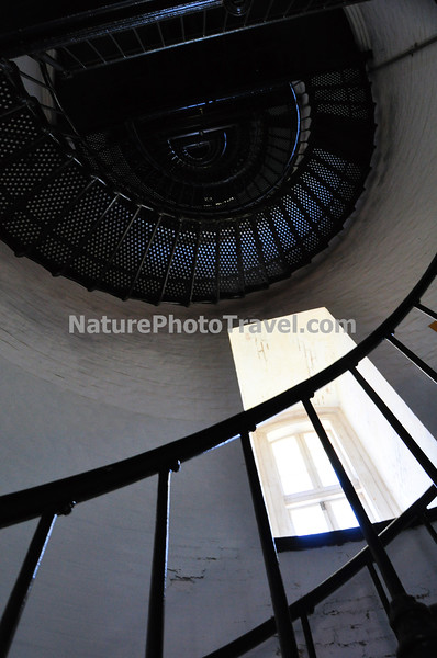 INTERIOR (Stairs) The current Bodie Island Lighthouse is the third that has stood in this vicinity of Bodie Island on the Outer Banks in North Carolina and was built in 1872. It stands 156 feet tall and is located on the Roanoke Sound side of the first island that is part of the Cape Hatteras National Seashore. The lighthouse is just south of Nags Head, a few miles before Oregon Inlet.<br /> <br /> BODIE ISLAND LIGHT FACTS:<br /> <br /> 1847 - The contractor on the first project was Mr. Francis Gibbons, of Baltimore, who would later become a prominent lighthouse builder on the West Coast. Cost was $5,000 but problems with location and design of the tower caused a ten year delay in construction. The tower was highly unstable and soon after it was completed, it began to lean toward the sea.<br /> 1859 - The Bodie Island Lighthouse had deteriorated and the Lighthouse Board secured a $25,000 appropriation from Congress to erect a new tower. This new tower was 80 ft (24 m). and its lantern was a third-order Fresnel lens.<br /> 1861 - In the fall of 1861, Confederate troops stacked explosives inside the tower and blew it apart.<br /> 1871 - A third lighthouse was completed in 1871 partially with material left over from construction of a new tower at Cape Hatteras. The tower was 156 ft (48 m). with a first order Fresnel lens that made its light visible for 18 nautical miles (33 km). The Bodie tower is painted with white and black horizontal bands