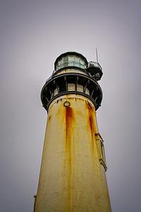 The Pidgeon Point lighthouse against the foggy sky