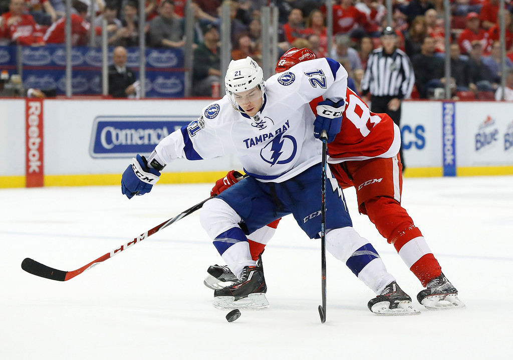 . Tampa Bay Lightning center Brayden Point (21) protects the puck from Detroit Red Wings left wing Tomas Nosek (83) in the second period of an NHL hockey game Friday, March 24, 2017, in Detroit. (AP Photo/Paul Sancya)