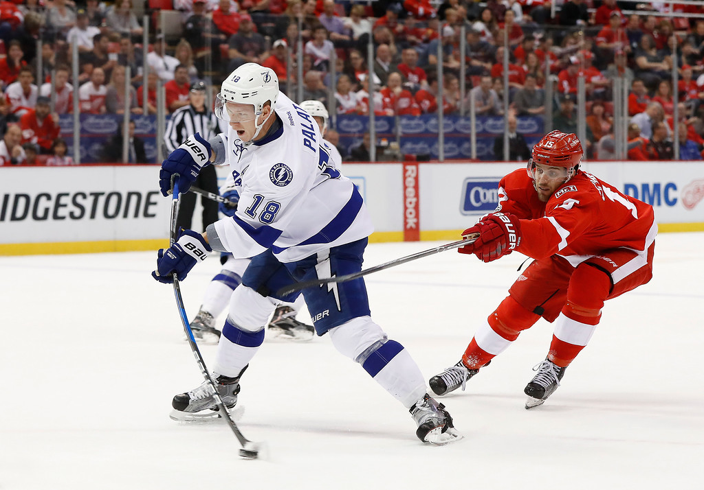. Tampa Bay Lightning left wing Ondrej Palat (18) shoots as Detroit Red Wings center Riley Sheahan (15) defends in the first period of an NHL hockey game Friday, March 24, 2017, in Detroit. (AP Photo/Paul Sancya)
