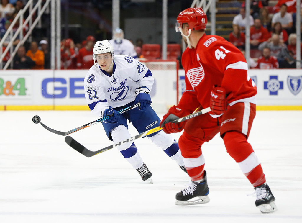 . Tampa Bay Lightning center Brayden Point (21) flips the puck past Detroit Red Wings center Luke Glendening (41) in the first period of an NHL hockey game Friday, March 24, 2017, in Detroit. (AP Photo/Paul Sancya)