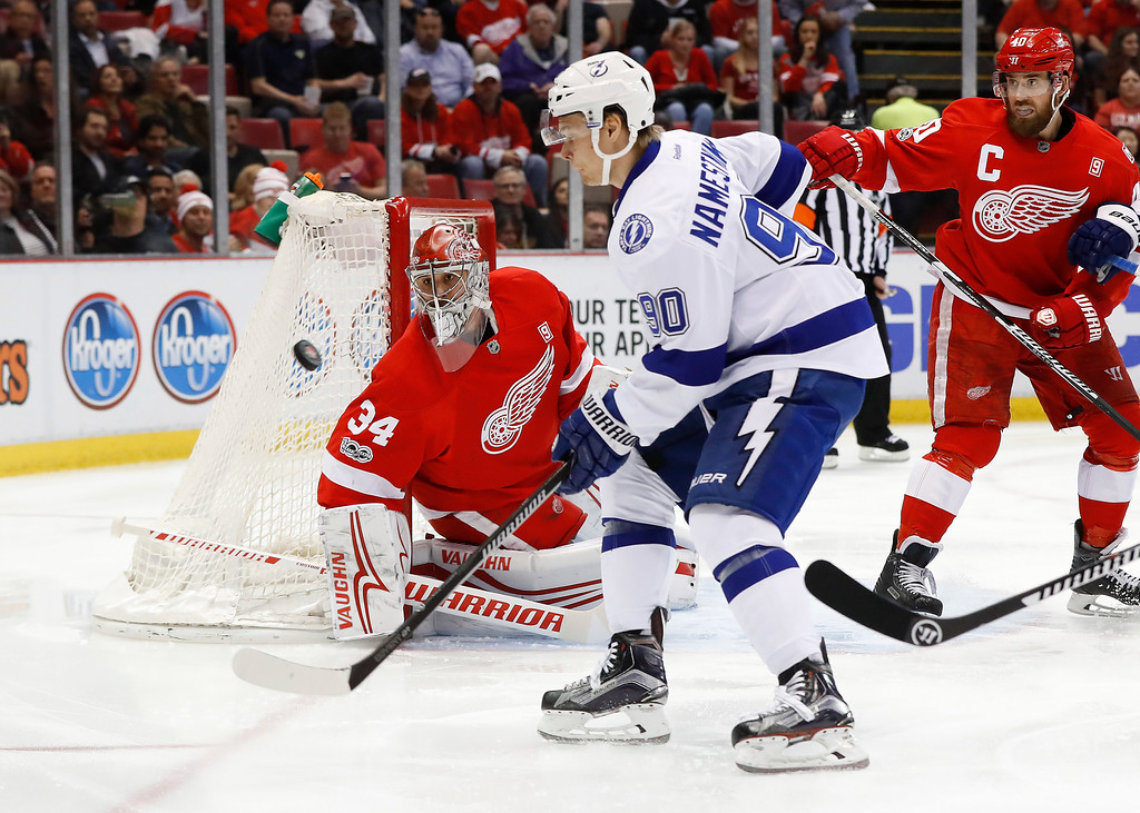 . Detroit Red Wings goalie Petr Mrazek (34) deflects the puck as Tampa Bay Lightning center Vladislav Namestnikov (90) pursues in the first period of an NHL hockey game Friday, March 24, 2017, in Detroit. (AP Photo/Paul Sancya)