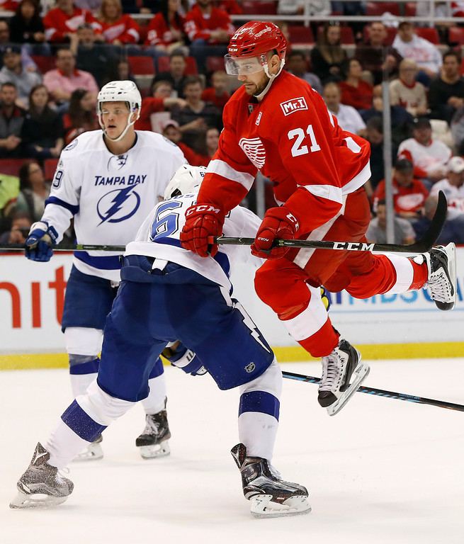 . Detroit Red Wings left wing Tomas Tatar (21) jumps to avoid Tampa Bay Lightning defenseman Andrej Sustr (62) in the second period of an NHL hockey game Friday, March 24, 2017, in Detroit. (AP Photo/Paul Sancya)