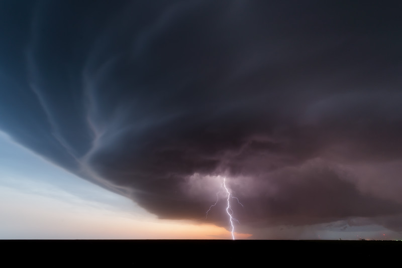 A cloud-to-ground lightning bolt strikes beneath a classic supercell near Winona, KS, at twilight on June 8, 2019.