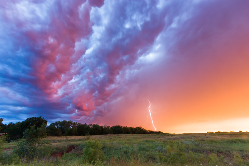 """Brilliant colors illuminate the """"whale's mouth"""" of a thunderstorm over Norman, OK, at sunrise on May 30, 2012."""
