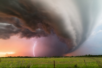 Lightning strikes within the rain core of a supercell thunderstorm at sunset near Petersburg, NE, on June 16, 2014.