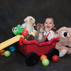 Baby seated in a red wagon with plastic balls and stuffed animals