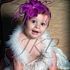 Little girl in a boa with a magenta head bow