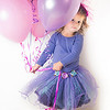 LIttle girl in a purple tutu holding a bunch of colorful birthday balloons