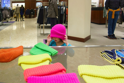 Lila trying on Winter hats at Neiman Marcus.   A little too big.