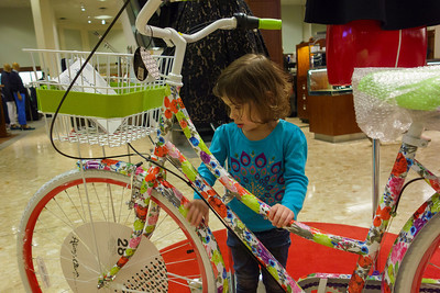 Lila checking out a bicycle at Neiman Marcus.