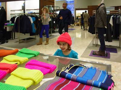 Lila trying on Winter hats at Neiman Marcus.