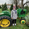 Mack Guthrie stands next to his family's vintage John Deere tractor.