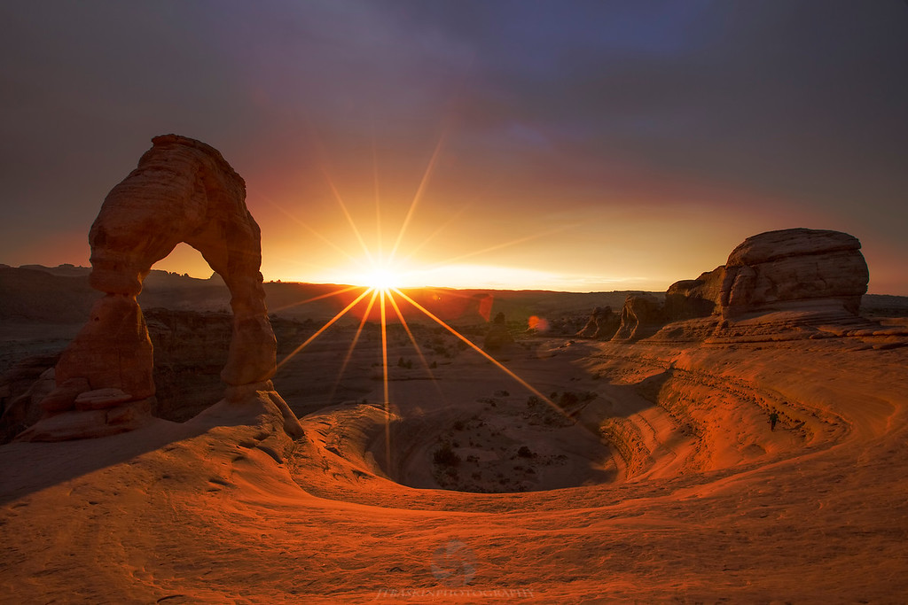 """Delicate Light - Arches National Park, UT<br /> IMG_0261<br /> <br /> This is the famous Delicate Arch. Just a short hike through Arches takes you to one the most amazing spots in the National Park System. And as such this landmark has been photographed to death. With that in mind, I had opted to head up here for some long exposure and moon light work after sunset. Then this happened! An explosion of wicked desert light and a sunburst you could see with the naked eye.... in short, a """"picture"""" perfect sunset. <br /> <br /> This image will be sold in a limited edition numbered to 100."""