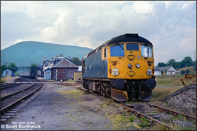 26035 stands dumped in a siding at Achnasheen after failing with a hot axle box whilst working 2K08 1045 Inverness-Kyle of Lochalsh on 25/07/1983. The stock off 2N20 1110 Kyle of Lochalsh-Inverness stands in the platform awaiting a rescue engine from Inverness after its locomotive, 37025 had been commandeered to work 26035's train forward to Kyle.