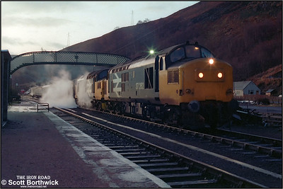 On a damp and miserable, not to mention cold winters morning, 37262+37114 stand at Garve with 2K02 0655 Inverness-Kyle of Lochalsh on 20/12/1984 awaiting the arrival of 37025 on 2N12 0710 Kyle of Lochalsh-Inverness in order that they can gain the single line westwards. The reason for the pair of 37s was 37262 had a working RETB set but no train heat, and 37114 had train heat but no RETB set. The pairing provided a sensible solution to the problem of keeping the passengers warm and having a loco able to operate the RETB signalling.