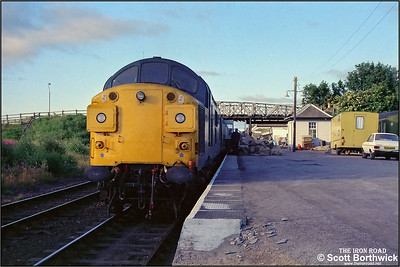 The mornings mail is unloaded at Dingwall as 37035 prepares to continue its journey to the Far North with 2K03 0640 Inverness-Wick on 21/07/1983.