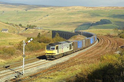 60066 runs off Dandry Mire viaduct and into Garsdale whilst working 6E13 1215 Newbiggin-Drax containerised gypsum empties on 18/10/2003.