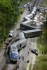 Law enforcement officers and railroad workers inspect the scene of a deadly wreck Tuesday May 6, 2003, near Hinesville, Ga. An Amtrak train collided with a lumber truck, killing the truck driver and critically injuring the train engineer. Amtrak train No. 91, known as the Silver Star, was en route from New York to Miami with about 150 passengers and 14 crew members. (AP Photo/Stephen Morton)