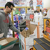 Stocking shelves at Gomes Liguors in Fitchburg is Eric Ahim. SENTINEL & ENTERPRISE/JOHN LIOVE