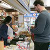 Mark Proctor of Lunenburg buys some beer at Peerless Liquors in Fitchburg Friday, March 20, 2020. He is being rung up by employee Nina Thirakoune. SENTINEL & ENTERPRISE/JOHN LIOVE