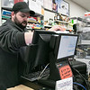 The staff at Gomes Liguors in Fitchburg wipe down all their surfaces all day long to try and stay safe. Wiping down the counter and computer is Jeremy Gale. SENTINEL & ENTERPRISE/JOHN LIOVE
