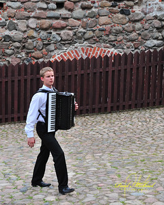 Trying to smuggle an accordion into the castle, but the guards noticed the worried look on his face.