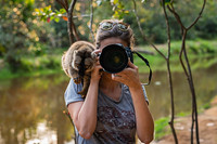 A photogapher with a monkey on their shoulder.