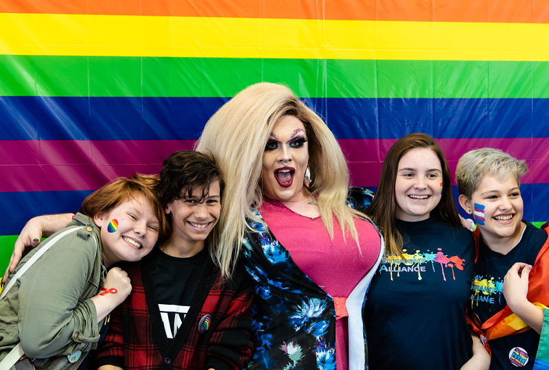 Attendees of the Little Apple Pride Parade pose with drag queen performer Olive D. Cox. Five drag queens performed on Saturday for a pavillion at Manhattan City Park full of individuals attending Little Apple Pride. (Olivia Bergmeier | Collegian Media Group)