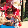 Francoise Carrier lends a helping hand to the children gathered for the ribbon cutting.