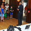 Ofc Lane demonstrates his belt of enforcement devices to Jr Dectives and their parents.