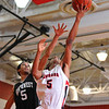 Cougars Charles Porter stretches for a layup as NW's Ramel Davidson defends