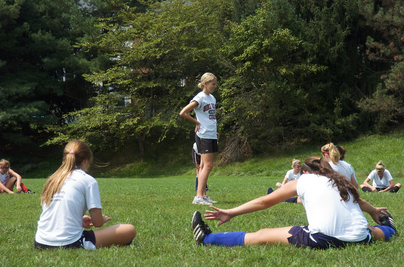 Fall Sports - QO 2010 to 2011.  Assistant Girls Soccer coach Allison O'Conner watches as the team goes through early season stretching drills.