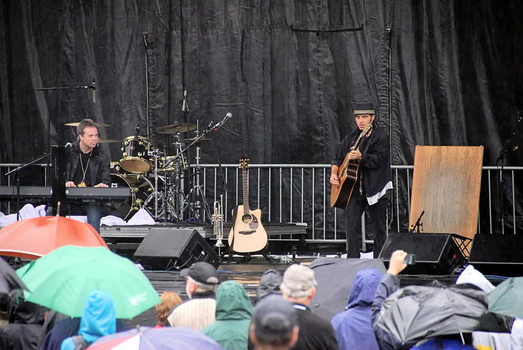 "This really gives you a feel for the day.  Nils had the crew back up the ""playing area"" and played all acoustic, never once plugging in the Fenders on the side of the stage.  I saw Bruce once at the Meadowlands get his hand burned from the bad mix of electricity and water...so Nils was being smart I guess.  Still, he could have tried an acoustic ""Because the Night:)"""