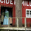 Women in period dress wait outside the 1860s cider mill.