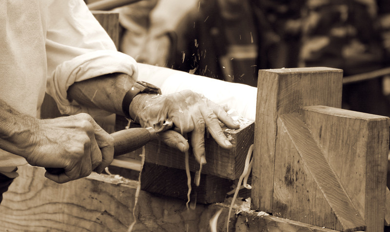 Splinters fly as rough, work-worn hands transform wood into a table leg using antique hand tools.