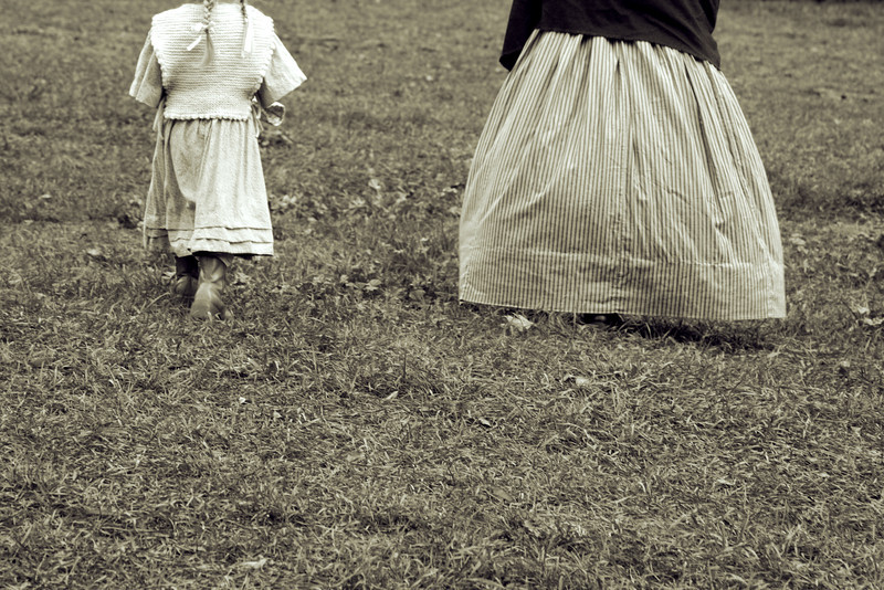 Woman and a young girl in period dress.