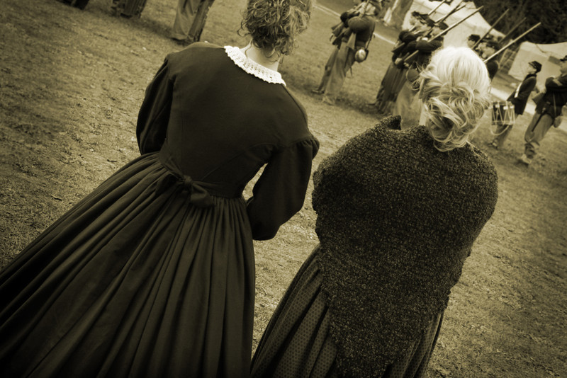 Women watch their brothers and lovers line up to go to war.