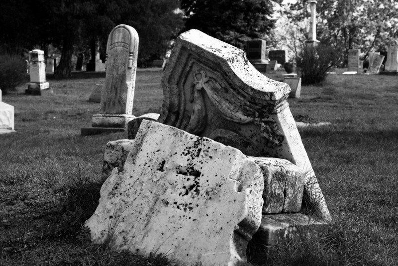 Cracked moss-covered headstone in an old graveyard.