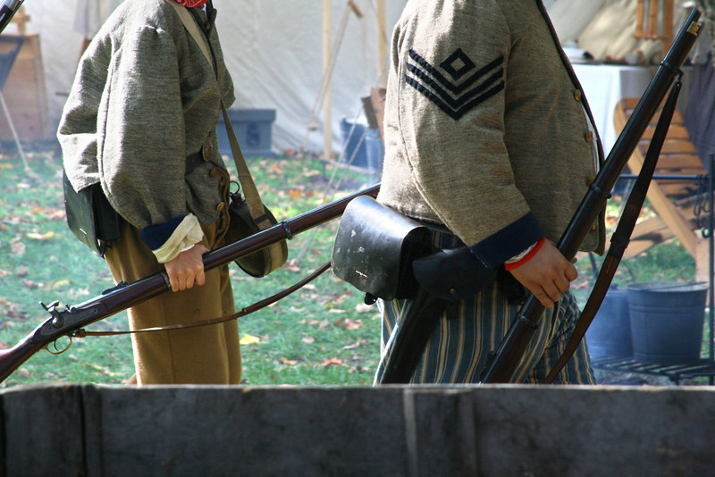 Civil war soldiers walk through camp.