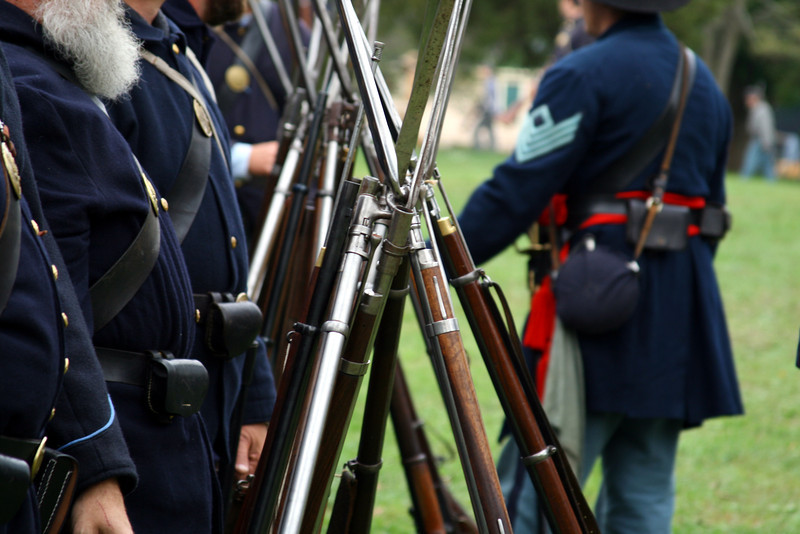 Muskets leaning in a tower as Union Civil War soldiers prepare for battle.