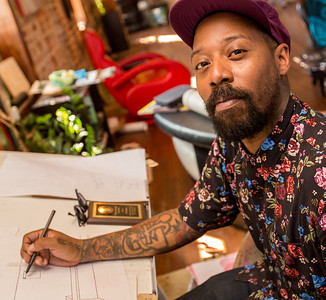 In one of several spaces where tattoo stations are located, Miya Bailey works on plans for coffee shop in the neighborhood beside a piece of his art that is ready to be framed.  Bailey is an entreprenuer, business owner and investor in Castleberry Hill.  He is a tattoo artist who owns City of Ink Tattoos and art galleries all along Walker Street.  (Jenni Girtman / Atlanta Event Photography)
