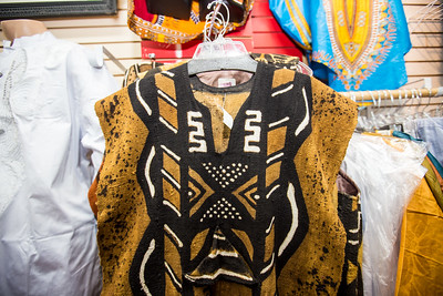 Traditional African fabrics and clothing are available at AfroCentric Network where fabrics from Ghana and Kenya are in great supply.  Agie Ngira is the store manager.  Mudcloth fabric is used on walets, vests and is sold as unaltered fabric, shown here.  (Jenni Girtman / Atlanta Event Photography)