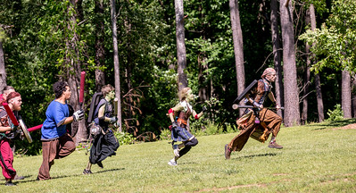 Twish aka Donovan Winters of Augusta, with rat on shield,  leads the pack, including Meredith Furbish, the green face named Slkie in the game, during a game of Capture the Flag at practice in Blackburn Park.  The live action game is a full-contact combat game that uses foam padded boffer weaponry. The High Spires is an official Dagorhir Battle Games chapter, focusing their efforts on veterans and new members.  (Jenni Girtman / Atlanta Event Photography)