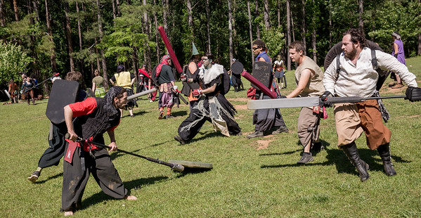 At the beginning of a new battle,  Red Raven, front left, Robert Gregory, and Fivel, front right, Josh Weinberg, get set and continue practice in Blackburn Park.  The local High Spires chapter practices on weekends.  The live action game is a full-contact combat game that uses foam padded boffer weaponry. The High Spires is an official Dagorhir Battle Games chapter, focusing their efforts on veterans and new members.  (Jenni Girtman / Atlanta Event Photography)