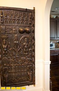 Jean-Patrick Guichard is a long-time collector of African art, he is at his Fairburn home, and plans a gallery opening in metro Atlanta in 2018.  This door on display next to the kitchen tells the creation story of the Dogon people in Mali.  Guichard was born in Africa and has pieces passed down from his mother as well as an expansive set of paintings, sculpture, ceremonial masks and artifacts he has secured through years of searching.  Many of the works are early works of now prolific and well known artists.  Guichard begins relationship at art school and art communities in Africa.  (Jenni Girtman / Atlanta Event Photography)