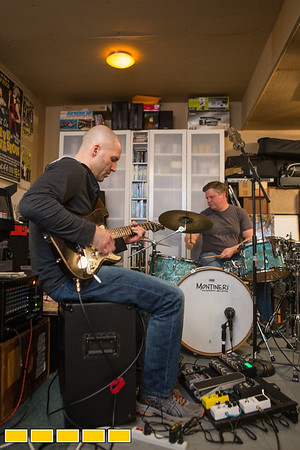 Neighbors, band mates and friends practice in the garage of the drummer, Elliott Danger, right, who is an estimator in commerical HVAC.  Guitar player Brian Creekmur, left, works in IT and bass guitarist and vocalist Brian Pollack, off camera right, is a Physician Scientist.  The group hopes to book local breweries and play events in their time off from their day jobs.  (Jenni Girtman / Atlanta Event Photography)