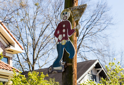 Where in Atlanta is this? In the residentail area a couple of blocks from busy shopping areas near Decatur Square, are these signs posted on telephone poles reminding drivers to Slow Down.  The well-weathered signs are on both sides of the street, some covered in vines and some with wooden pieces missing.  (Jenni Girtman / Atlanta Event Photography)